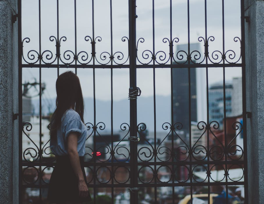 woman standing next to wrought iron fences