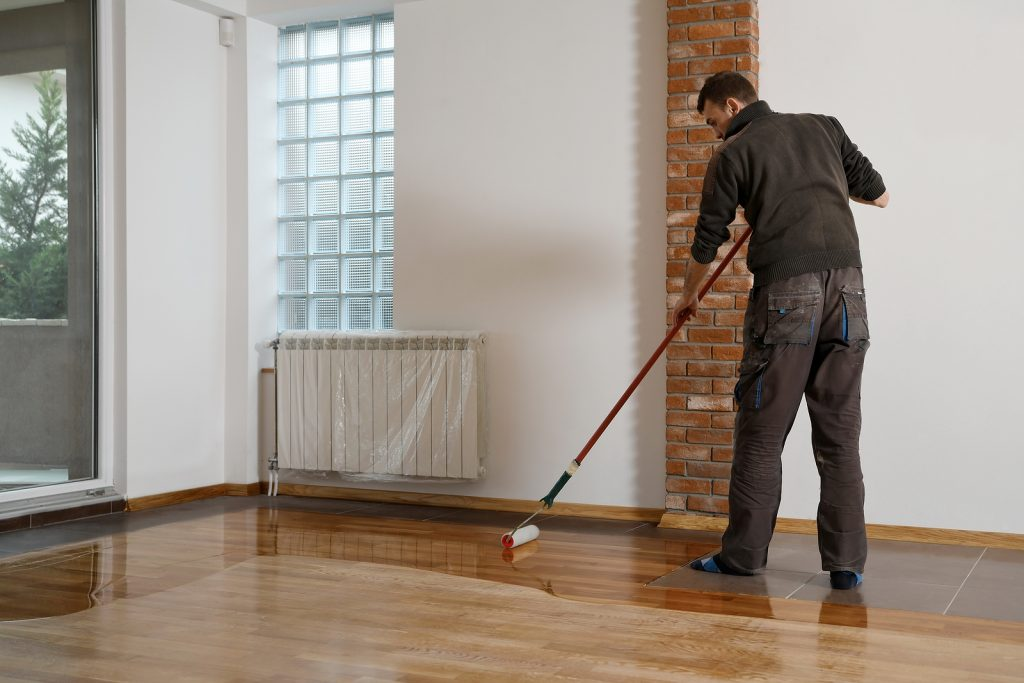 Worker uses a roller to coat timber floors.