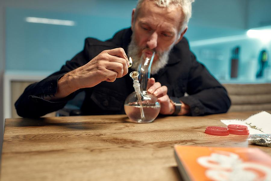 Senior man lighting cannabis in a small bong